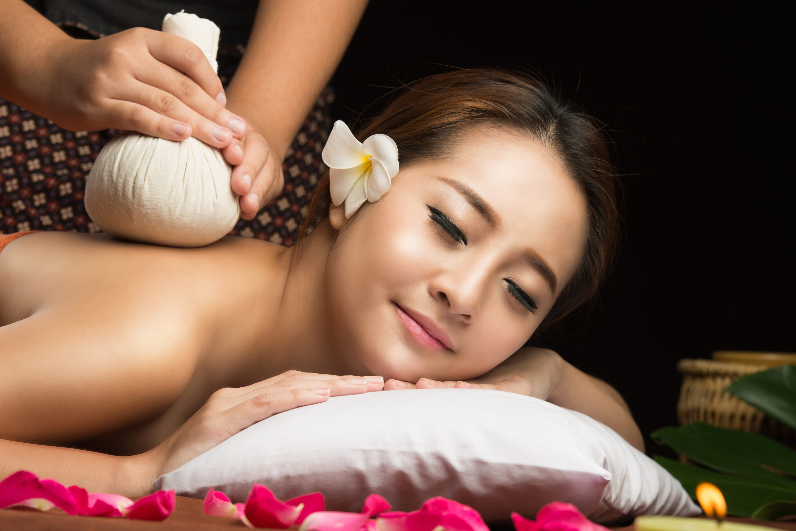 Asian woman getting thai herbal compress massage in spa.She is v